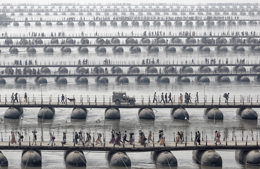 Pilgrims and devotees cross pontoon bridges at the Maha Kumbh Mela - the largest spiritual gathering on the planet, held every 12 years in India